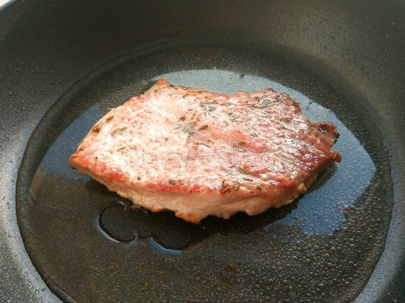 Organisches gekochtes gebratenes Schweinekotelett-Steakfleisch mit solt, Pfeffer, Rosmarin und Öl auf schwarzem Bratpfannenhinter lizenzfreie stockfotos