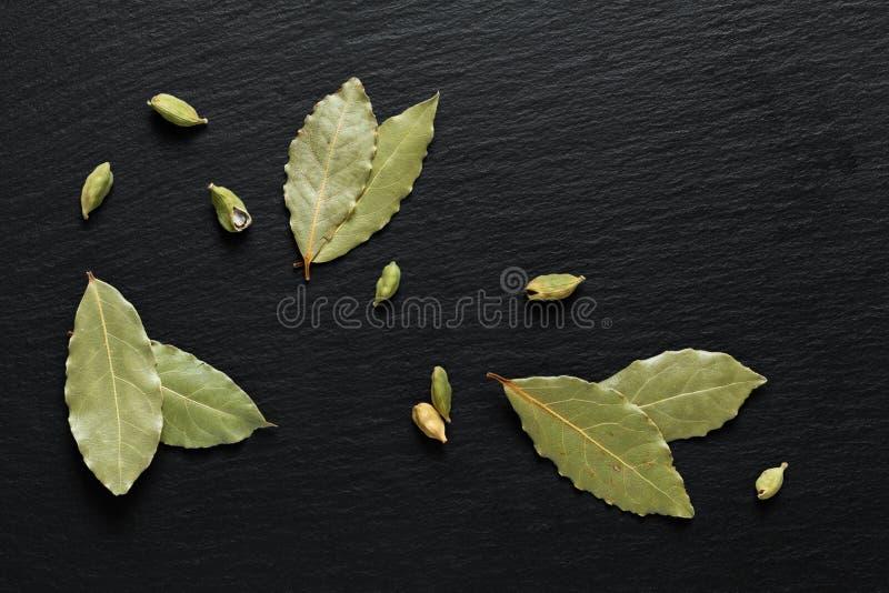 Organisches getrocknetes Lorbeerblatt Nahrungsmitteldes grünen Hintergrundkonzeptes mit Kardamomhülsen auf schwarzem Schieferstei stockfotos