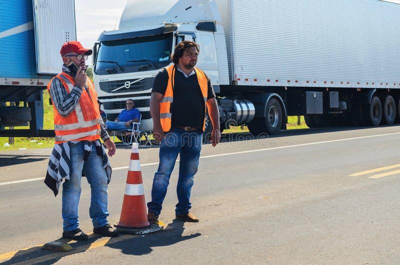 Organiserande trafik för folk på huvudvägen på de stoppade lastbilarna p arkivbilder