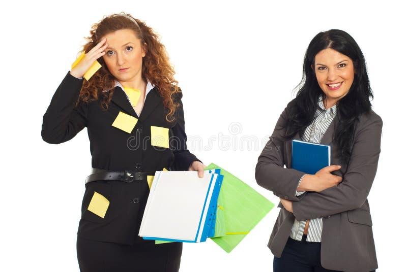 Organisierte und durcheinandergebrachte Geschäftsfrauen stockfotos