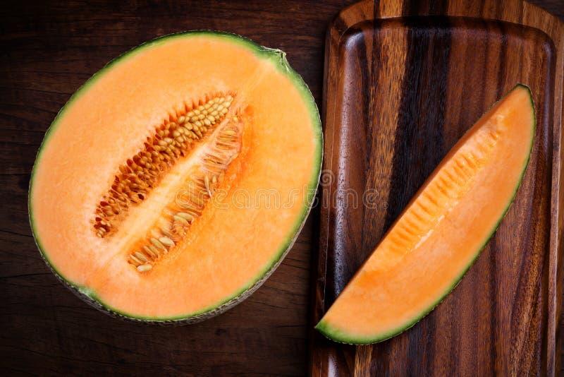 Organisk cantaloupmelon med redskap på trätabellen royaltyfria bilder