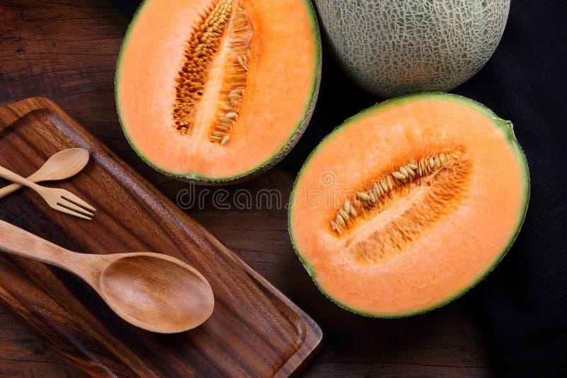 Organisk cantaloupmelon med redskap på trätabellen arkivfoton