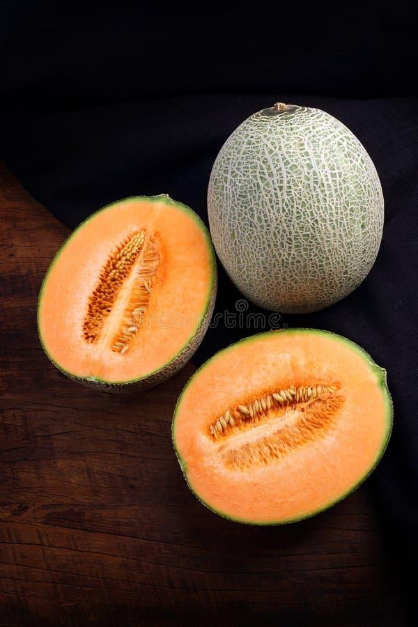 Organisk cantaloupmelon på trätabellen royaltyfria bilder