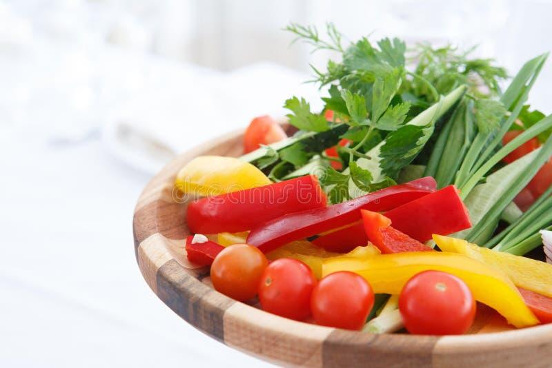 Organisk lantg?rd Nya grönsaker i träplatta: gul och röd spansk peppar, lök, tomat och gurkor royaltyfri fotografi