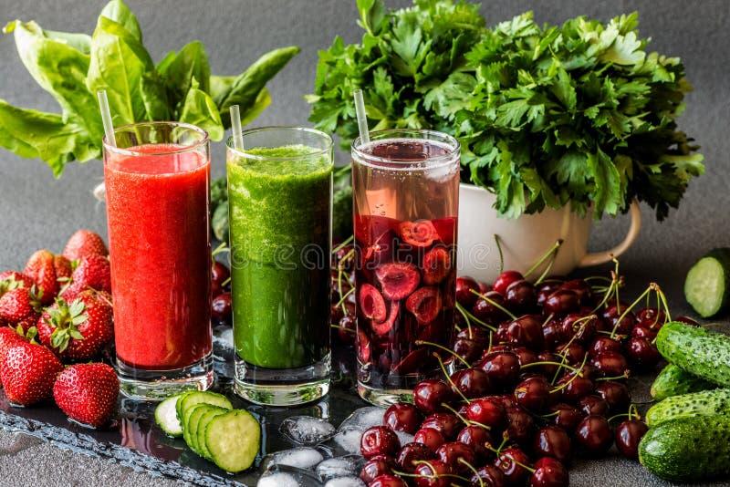 Organisk mat som isoleras på grå bakgrund Detoxvatten med körsbär och den gröna smoothien med ingredienser Sunda detoxdrinkar arkivbilder
