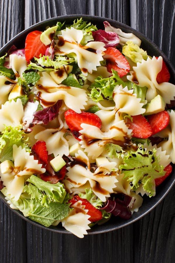 Organisk pastafarfallesallad med avokadot, jordgubbar, grönsallat, påklädd med balsamic såsnärbild Vertikal b?sta sikt arkivfoton
