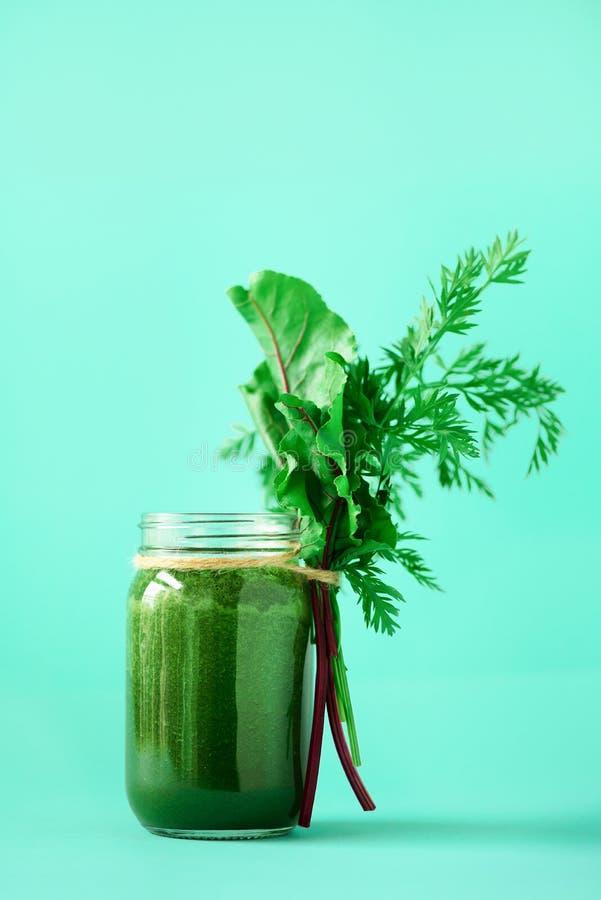 Organisk smoothie med betagräsplaner och morotblast på blå bakgrund, kopieringsutrymme Sunt äta för detox som är alkaliskt bantar arkivbild