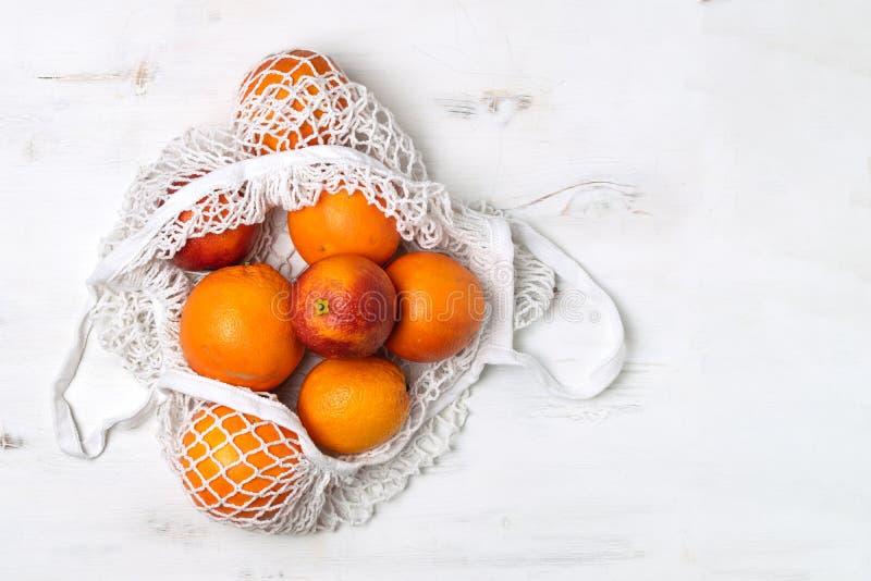 Organiska blodiga apelsiner i den återvinningsbara påsen för bomullsingrepp, gul bakgrund - återanvända, hållbar livsstil, nollav royaltyfria bilder