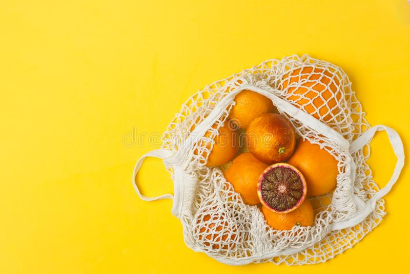 Organiska blodiga apelsiner i den återvinningsbara påsen för bomullsingrepp, gul bakgrund - återanvända, hållbar livsstil, nollav arkivfoto