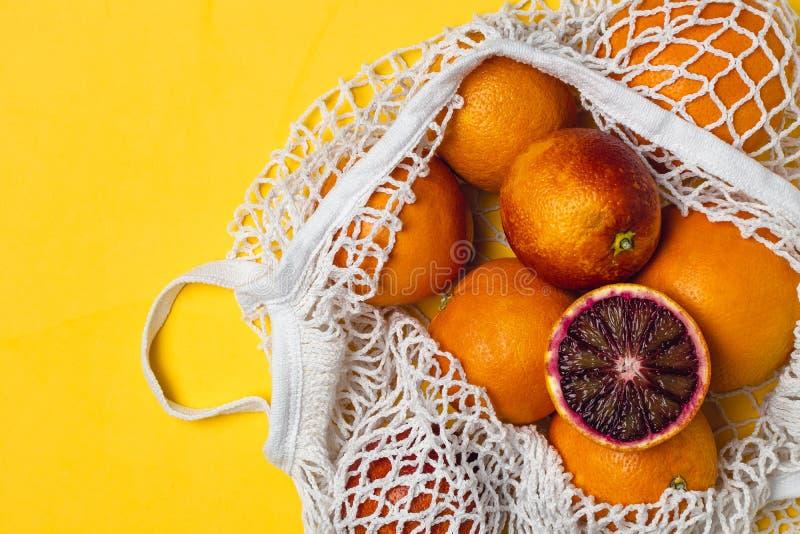Organiska blodiga apelsiner i den återvinningsbara påsen för bomullsingrepp, gul bakgrund - återanvända, hållbar livsstil, nollav fotografering för bildbyråer