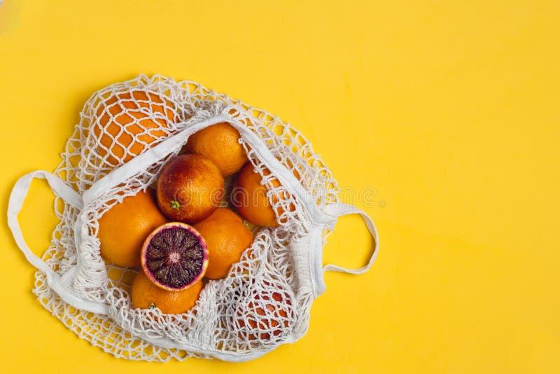 Organiska blodiga apelsiner i den återvinningsbara påsen för bomullsingrepp, gul bakgrund - återanvända, hållbar livsstil, nollav arkivbilder