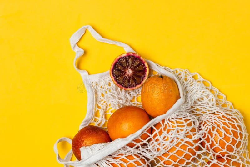 Organiska blodiga apelsiner i den återvinningsbara påsen för bomullsingrepp, gul bakgrund - återanvända, hållbar livsstil, nollav arkivbild