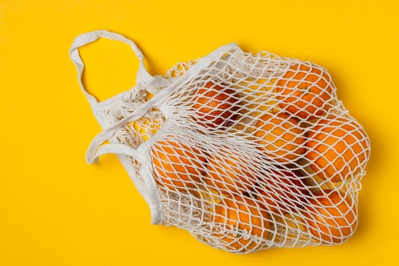Organiska blodiga apelsiner i den återvinningsbara påsen för bomullsingrepp, gul bakgrund - återanvända, hållbar livsstil, nollav royaltyfria foton