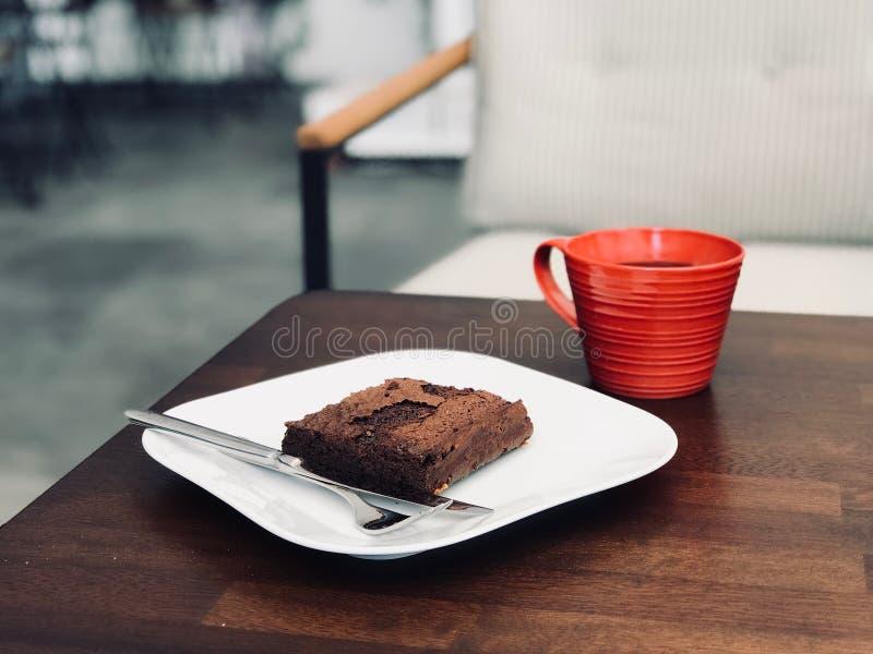 Organiska Brownie Chocolate Cake/ingen fri efterrätt för mjölgluten med den röda kaffekoppen fotografering för bildbyråer