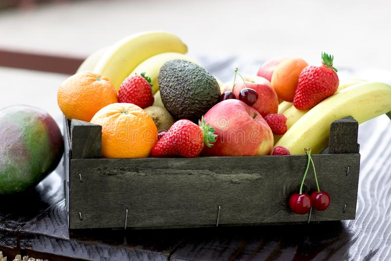 Organiska frukter för artistisk frukt i en träspjällåda royaltyfri fotografi
