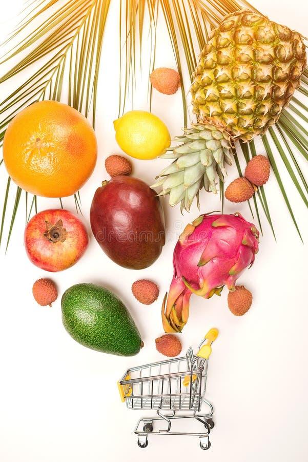 Organiska frukter som faller in i den mini- shoppa vagnen Organiskt marknadsbegrepp Exotiska tropiska frukter på vit bakgrund liv royaltyfri foto
