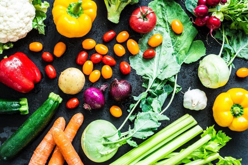 Organiska grönsaker för ny färgrik vår på svart royaltyfri fotografi