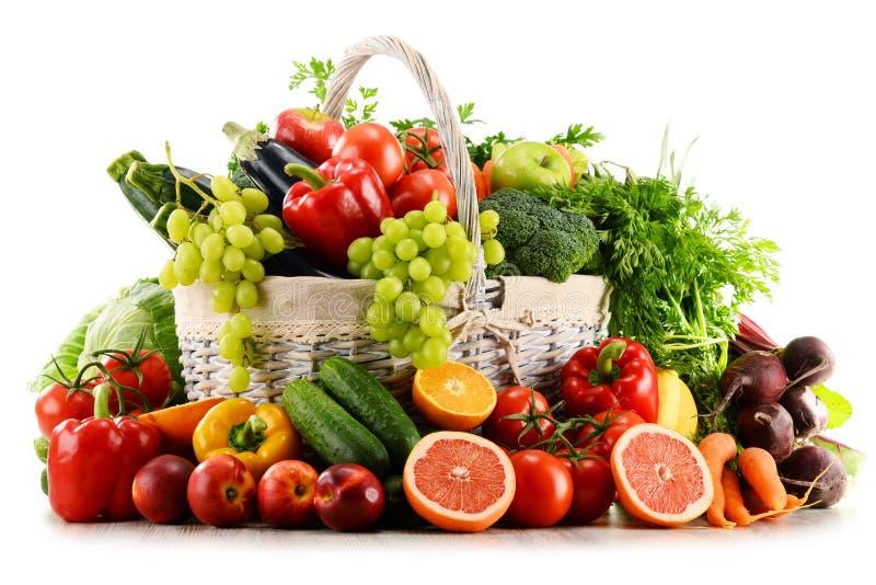Organiska grönsaker och frukter i vide- korg på vit fotografering för bildbyråer
