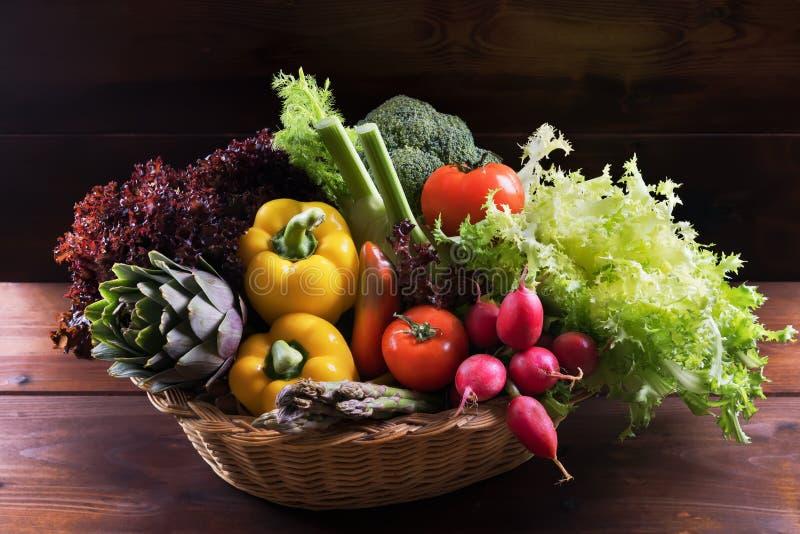 Organiska nya grönsaker i korg på mörk träbakgrund, sund mat och rent ätabegrepp arkivbild