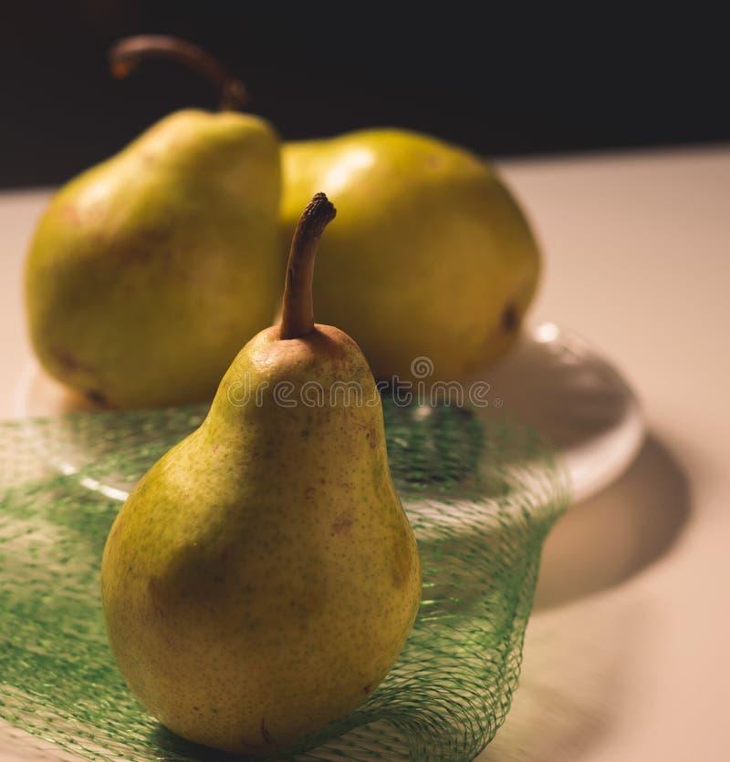 Organiska päron på en vit platta, främre sikt arkivfoton
