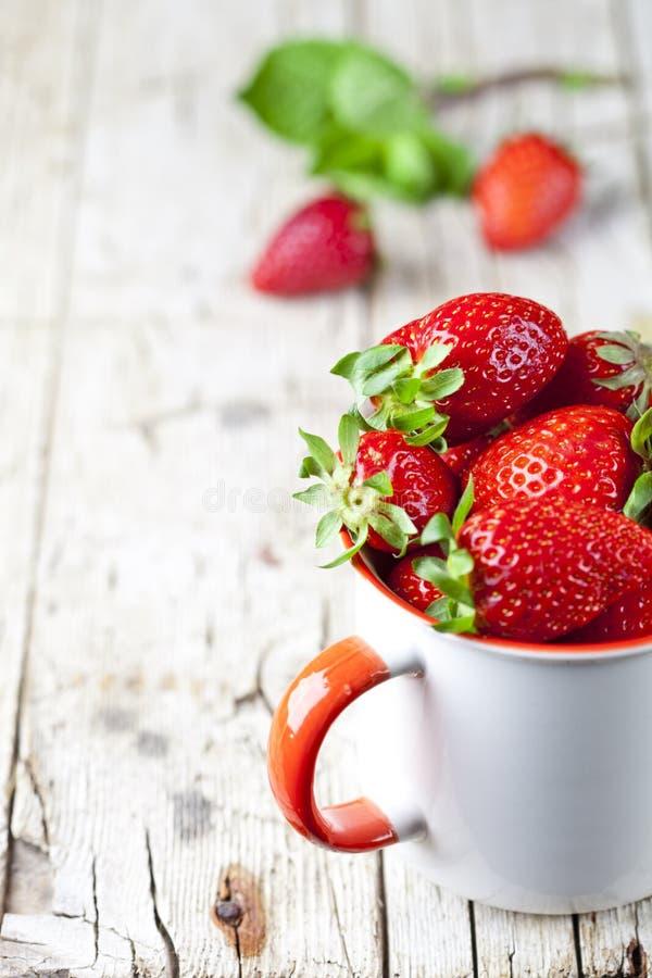 Organiska r?da jordgubbar i den vita keramiska koppen p? lantlig tr?bakgrund royaltyfri bild