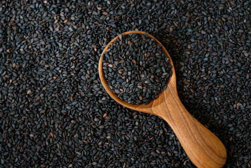 Organiskt frö för a-svartsesam i träsked, sund mat för förminskningar i både systolic och diastolic blodtryck royaltyfri bild