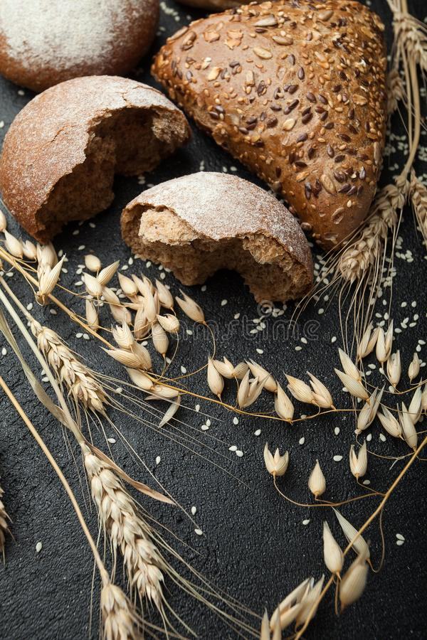 Organiskt nytt bröd och vete på en svart bakgrund som är vertikal royaltyfri fotografi