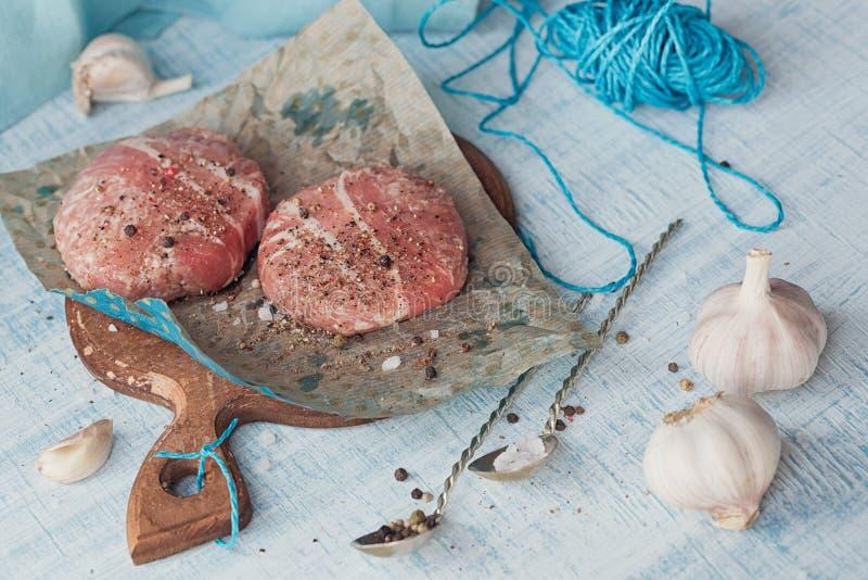 Organiskt rått jordnötkött som slås in i remsor av bacon arkivbilder