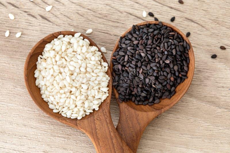 Organiskt svartvitt sesamfrö i en träsked, en sund mat för förminskningar i både systolic och diastolic blodtryck royaltyfria bilder