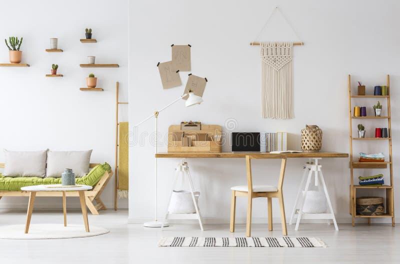 Organizador interior da mesa do escritório domiciliário natural, macramê em uma parede, prateleiras e sofá fotografia de stock