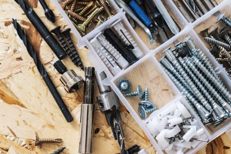 Organizador transparente plástico com parafusos, passadores, brocas, bocados no fundo do OSB imagens de stock