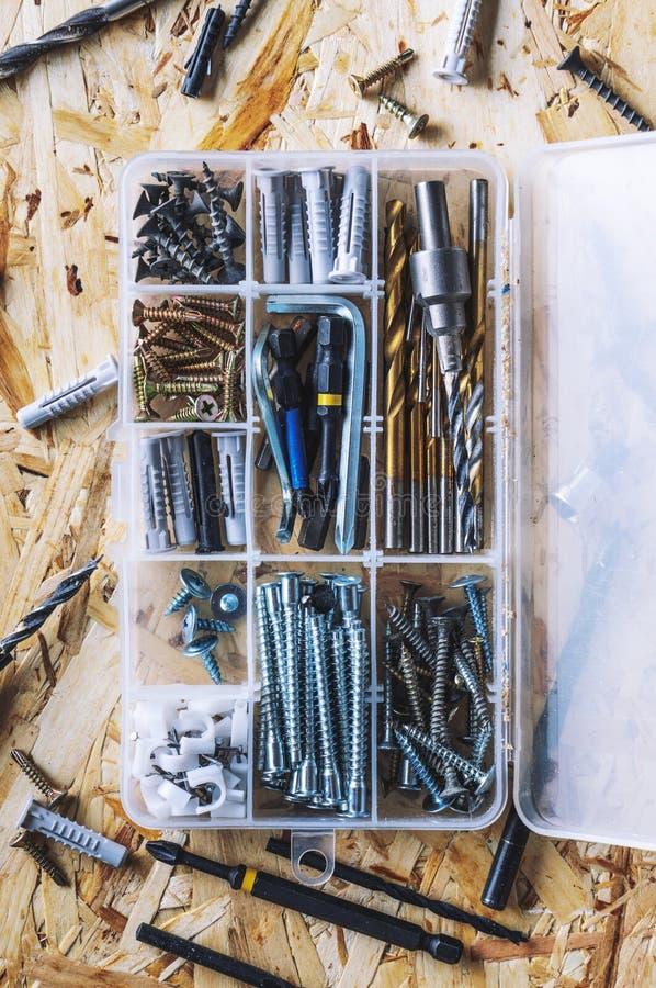 Organizador transparente plástico com parafusos, passadores, brocas, bocados no fundo do OSB foto de stock