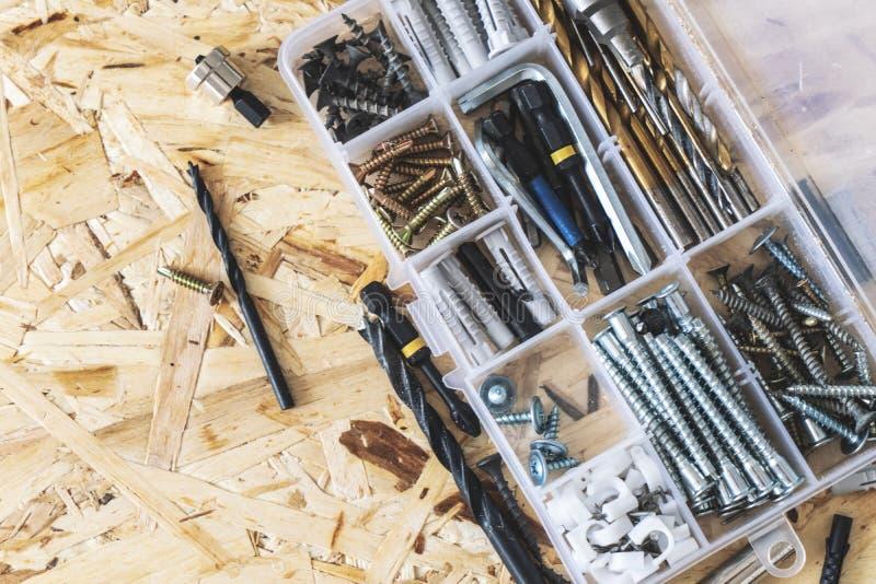 Organizador transparente pl?stico com parafusos, passadores, brocas, bocados no fundo do OSB fotografia de stock