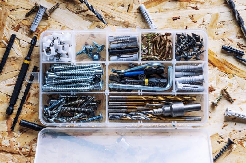 Organizador transparente pl?stico com parafusos, passadores, brocas, bocados no fundo do OSB fotos de stock royalty free