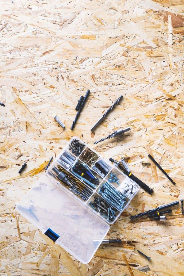 Organizador transparente pl?stico com parafusos, passadores, brocas, bocados no fundo do OSB fotos de stock