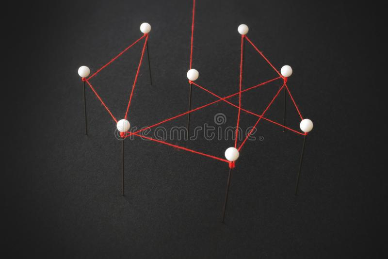 Organizational structure or social network concept with pins and thread illustrating linkages stock photography