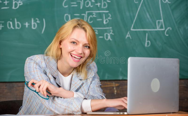 Organize class and make learning easy process. Teacher woman sit table work laptop surfing internet chalkboard stock photo