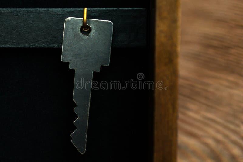 Organize seu conceito da vida, do seguro e da segurança: uma suspensão chave no gancho dourado em um CCB chave do armário da caix imagens de stock