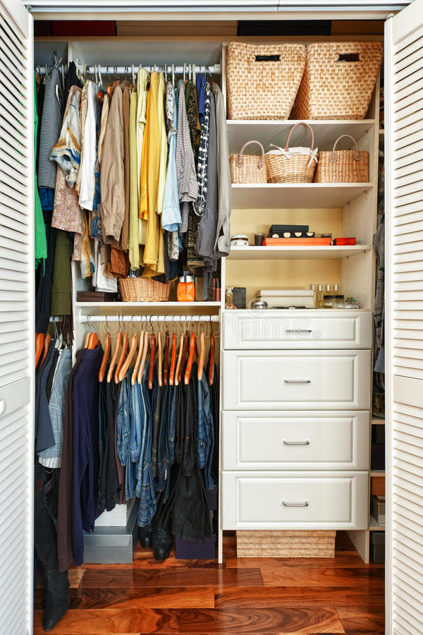 Organized closet. Clothes hung neatly in organized closet at home stock photography