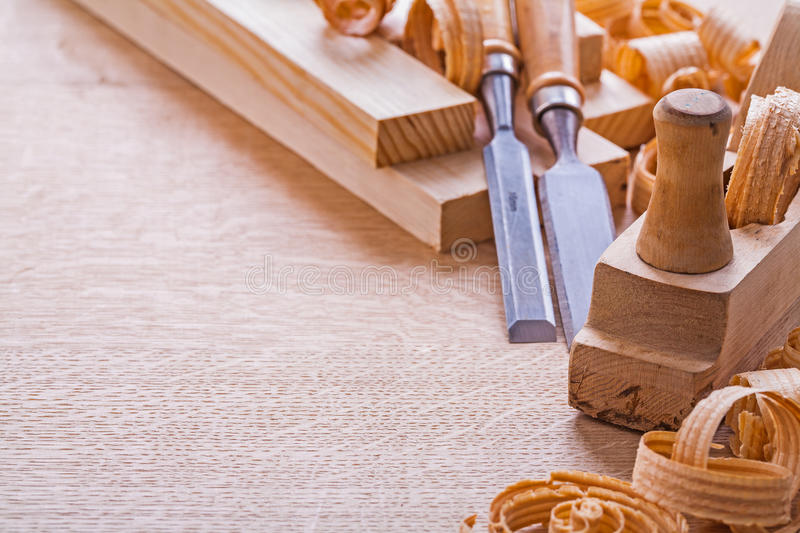 Organized copspace woodworkers plane carpentry. Chisels shavings on wooden board construction concept stock image