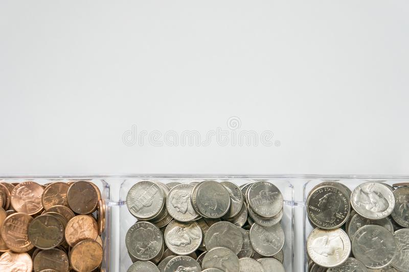 Organized loose coin change on bottom side, blank empty room space for text top. Isolated organized loose coin change on bottom side, white background, blank stock image