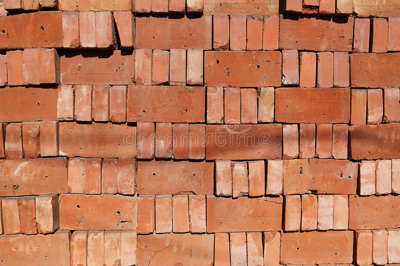 A organized pile of loose red bricks stacked on top of each other stock photos