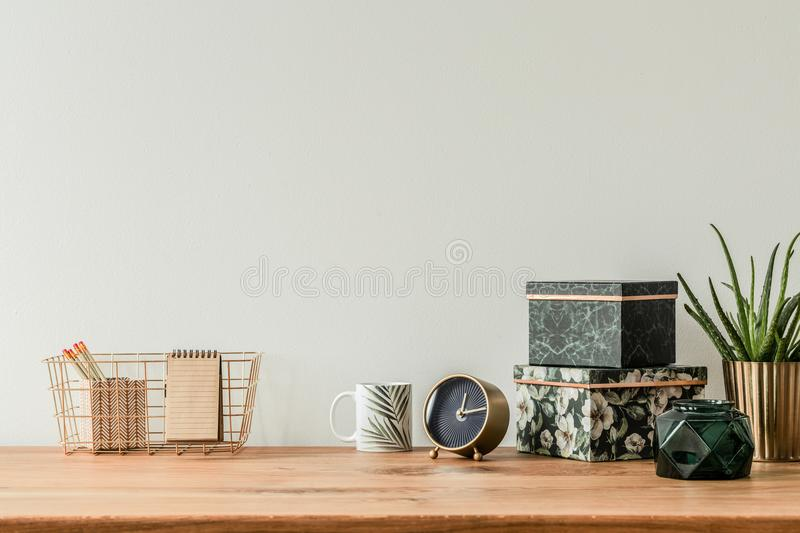 Organized table top. With floral boxes, mug, clock and metal box on an empty wall stock photo