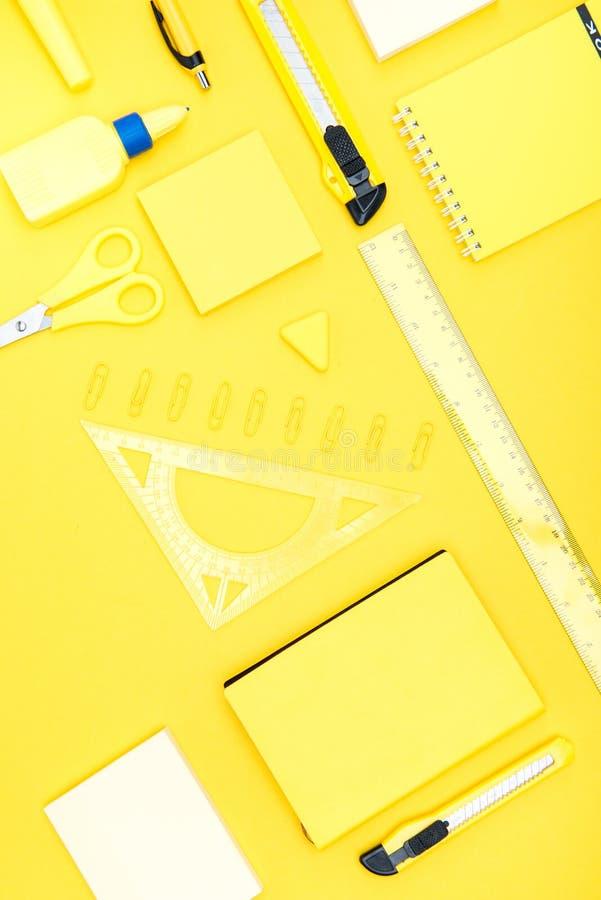 Organized various office supplies on yellow. Top view of organized various office supplies on yellow stock photo
