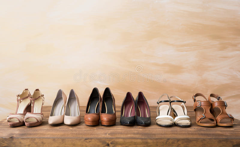 Organized woman`s shoes on wooden floor. Organized woman`s shoes on wooden table royalty free stock image