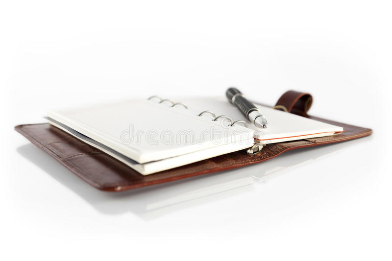 Organizer and pen. Open personal organizer, with pen, on white background royalty free stock photos