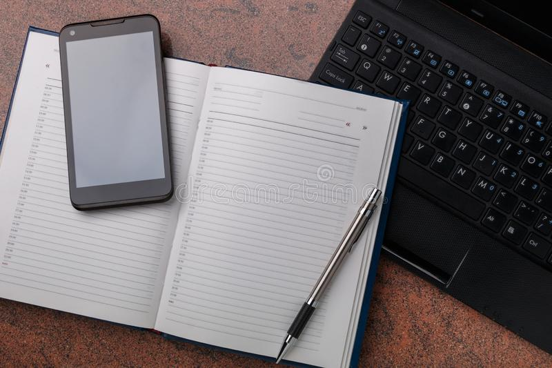 Organizer with smartphone and laptop computer on granite surface stock photo