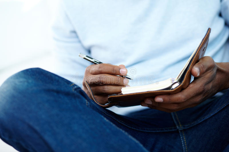 Organizing work. Hands of young African man writing something in notepad stock photos