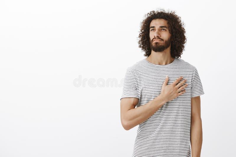 Orgulhoso de meu país Retrato do homem oriental thoutful considerável com barba e cabelo encaracolado, guardando a palma no coraç foto de stock royalty free