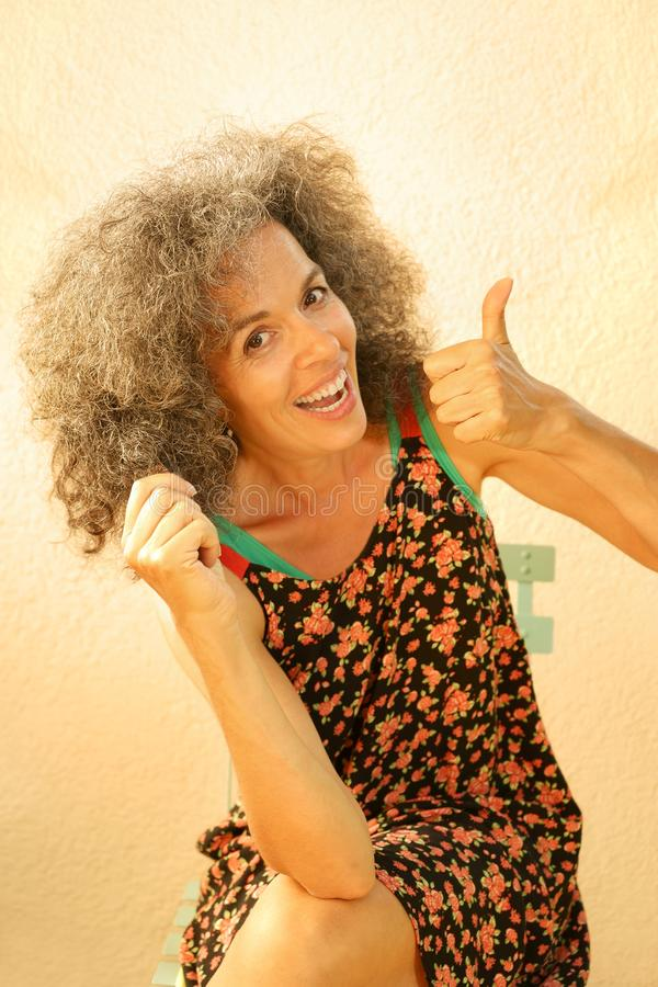 Orgullo del sorbo del pulgar de la mujer 50+ en su pelo graying imagen de archivo libre de regalías